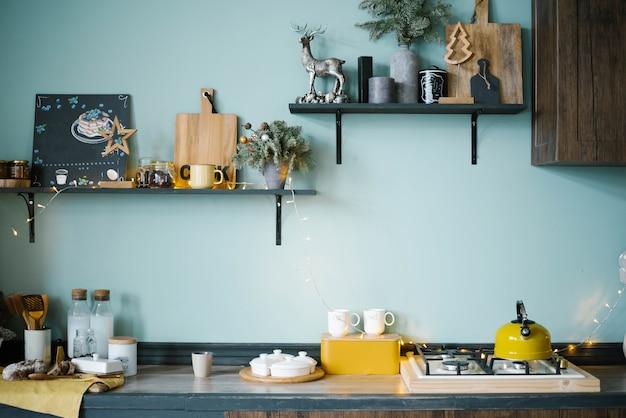 Feestelijk ingerichte houten keuken met blauwe wanden in scandinavische stijl
