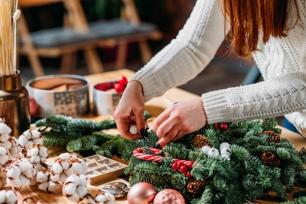 Feestelijk interieur. close-up van professionele bloemisthanden die groen sparrentakje, katoenplant gebruiken om kerstmisdecor te creëren.