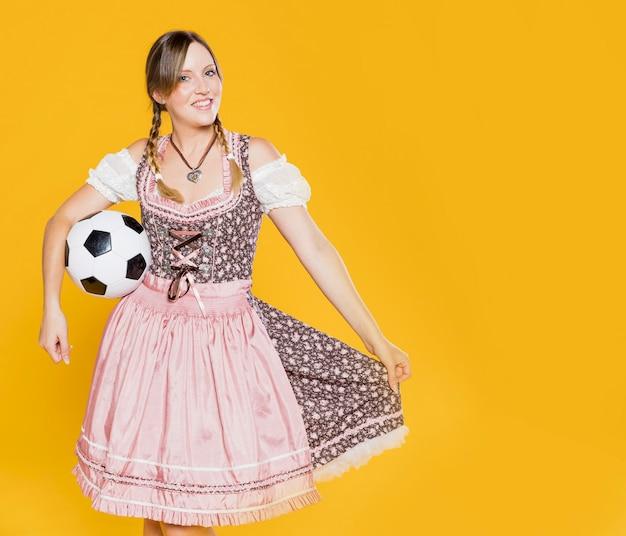 Feestelijk jong meisje met voetbal