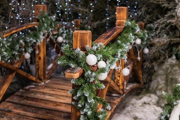 Feestelijk kerstdecor nabij het huis. straatdecoratie voor de wintervakantie. eerste takken met witte kerstballen sierlijke de houten brug in de tuin. concept happy christmas, nieuwjaar.