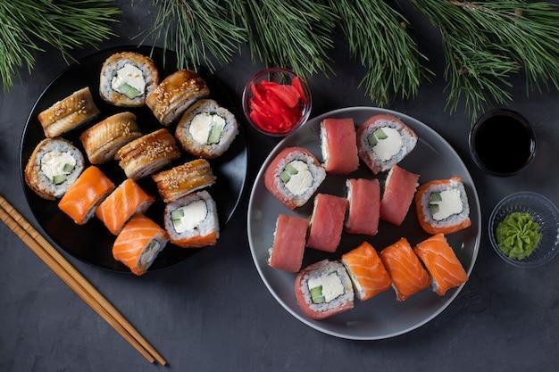 Feestelijk kerstdiner met sushi van zalm, tonijn en paling met philadelphia kaas. bovenaanzicht op donkere achtergrond