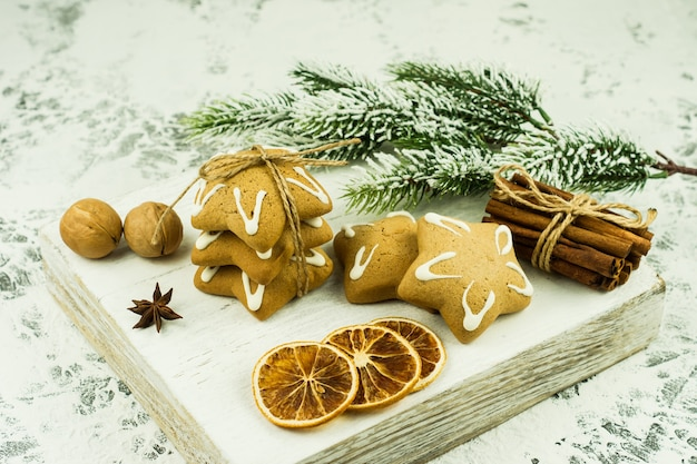 Feestelijk kerstvoedsel op houten bureau. gedroogde ornges, kaneelstokjes, walnoten en anijssterren versierde dennenboomtak.
