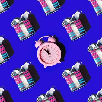 Feestelijk naadloos patroon van kerstcadeaus en roze wekker op een blauwe achtergrond, vierkante lay-out, bovenaanzicht. kan worden gebruikt als kerst- en nieuwjaarskaarten, achtergrond voor ontwerp, inpakpapier