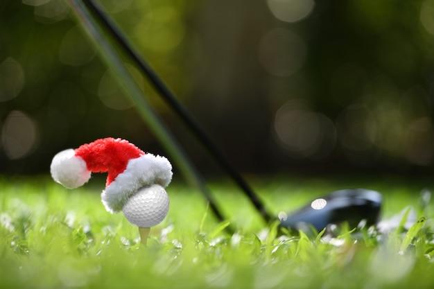 Feestelijk ogende golfbal op t-stuk met de hoed van de kerstman erop voor vakantieseizoen op golfbaanachtergrond