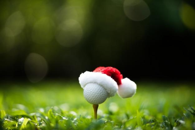 Feestelijk ogende golfbal op t-stuk met kerstmuts bovenop voor vakantieseizoen op golfbaan