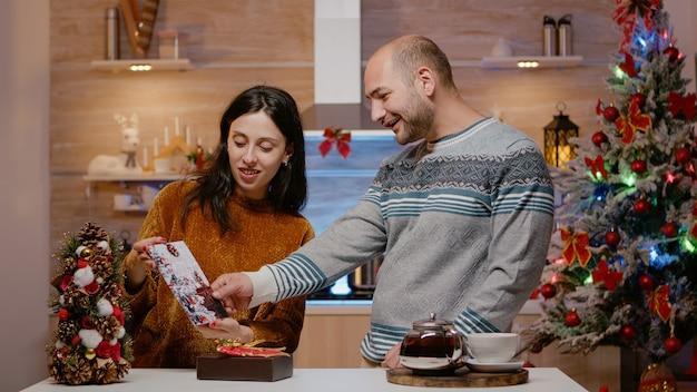 Feestelijk paar dat cadeau en kerstkaart voorbereidt