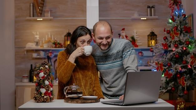 Feestelijk paar dat videogesprekcommunicatie op laptop gebruikt