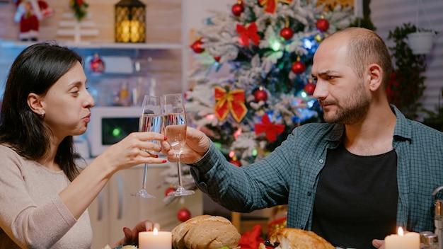Feestelijk paar genieten van kerstdiner en rammelende glazen