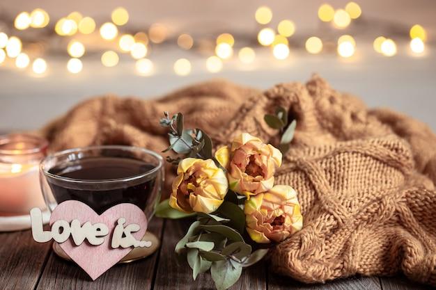Feestelijk stilleven hou ervan met een drankje in een kopje, bloemen en decordetails op een houten oppervlak tegen een onscherpe achtergrond met bokeh.