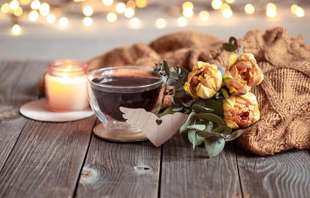 Feestelijk stilleven met een drankje in een kopje, bloemen en een gebreid item op een houten ondergrond tegen een onscherpe achtergrond met bokeh.