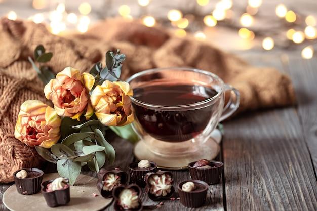 Feestelijk stilleven met een drankje in een kopje, chocolaatjes en bloemen op een onscherpe achtergrond met bokeh.