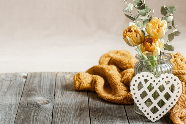Feestelijk stilleven voor valentijnsdag met bloemen in een vaas, gebreid element en decoratief hart op een houten oppervlak close-up.