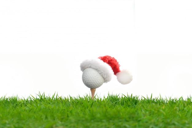 Feestelijk uitziende golfbal op t-stuk met de hoed van santa claus op bovenkant voor vakantieseizoen op wit wordt geïsoleerd dat