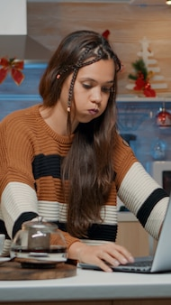 Feestelijk volwassen typen op laptop zittend in de keuken