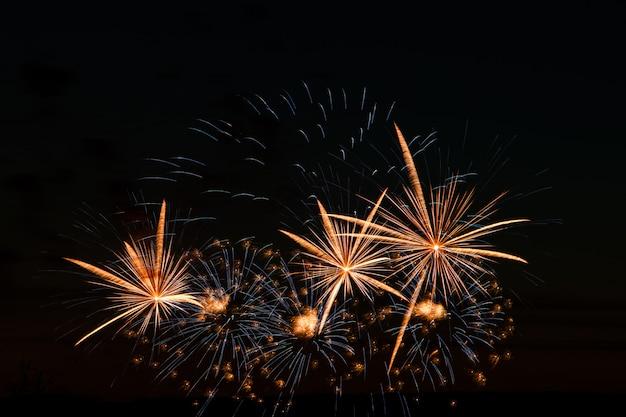 Feestelijk vuurwerk in de nachtelijke hemel. heldere veelkleurige begroeting op een zwarte achtergrond. plaats voor tekst.
