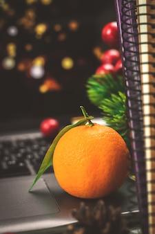 Feestelijk winterstilleven met mandarijn of tangerin op achtergrond van boeken, laptop en garlad bokeh, vakantie thuis. hoge kwaliteit foto