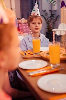 Feestelijke aandacht. knappe jongen zit in het midden van de tafel terwijl hij pizza gaat eten