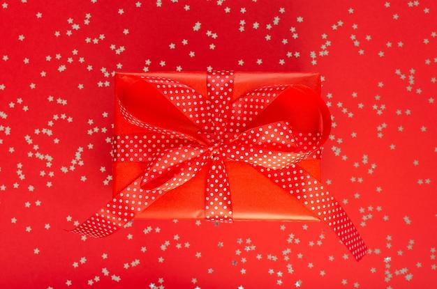 Feestelijke achtergrond, geschenkdoos met lint en strik op een rode achtergrond met glitter zilveren sterren, plat gelegd, bovenaanzicht