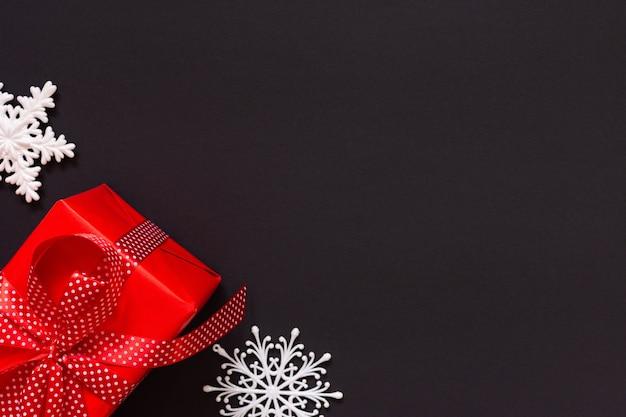 Feestelijke achtergrond met cadeau, rode geschenkdoos met lint in polka dots en boog en sneeuwvlokken op zwarte achtergrond, zwarte vrijdag concept, plat lag, bovenaanzicht