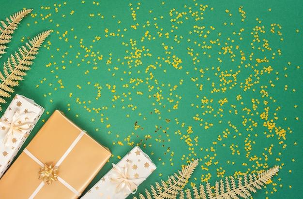 Feestelijke achtergrond met versieringen, heldere glanzende gouden varenbladeren en geschenkdozen op een groene achtergrond met glitter gouden sterren, plat lag, bovenaanzicht, kopieer ruimte