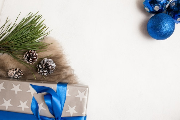 Feestelijke achtergrond van kerstcadeautjes. verpakte geschenkdoos, ornament blauwe ballen en strobila met bont en dennen, bovenaanzicht met kopie ruimte in het midden. felicitatie en handgemaakt decorconcept
