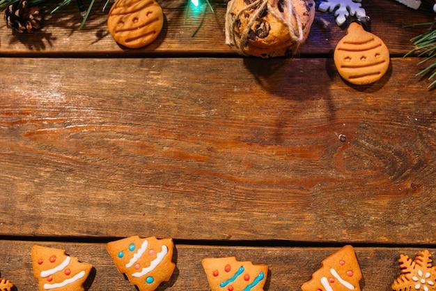 Feestelijke achtergrond van kerstmis bekary. bovenaanzicht zelfgemaakte peperkoekkoekjes en pijnboomtak op houten achtergrond, vrije ruimte in het midden.