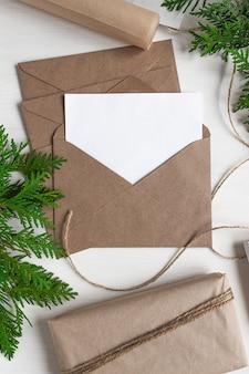 Feestelijke achtergrond van natuurlijk materiaal voor kerstmis en nieuwjaar geopende ambachtelijke envelop met