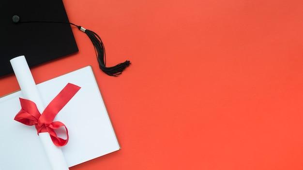 Feestelijke afstudeersamenstelling op rode achtergrond met exemplaarruimte