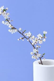 Feestelijke ansichtkaart met verse natuurlijke bloeiende kersenbloemen tak in een keramische vaas