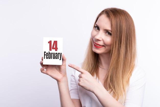 Feestelijke banner met vrouw handen met gloeiende lightbox met tekst love is in the air op heldere blauwe achtergrond voor valentijnsdag. flatlay-banner voor 14 februari. bovenaanzicht. copyspace.