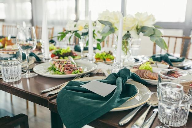 Feestelijke bruiloftstafel versierd met groene servetten en kaarsen