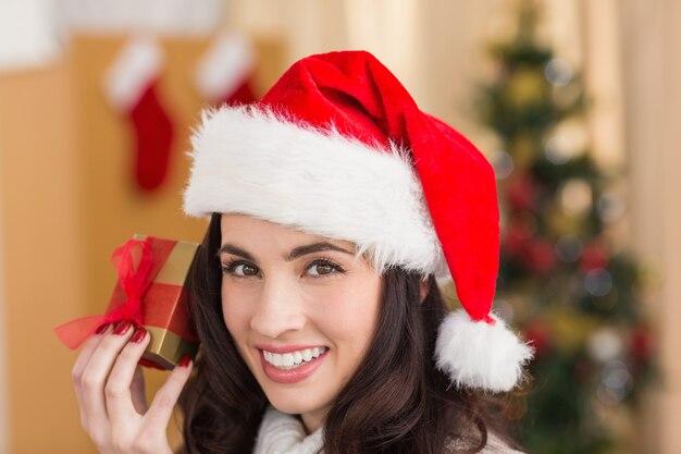 Feestelijke brunette die gift toont bij chistmas