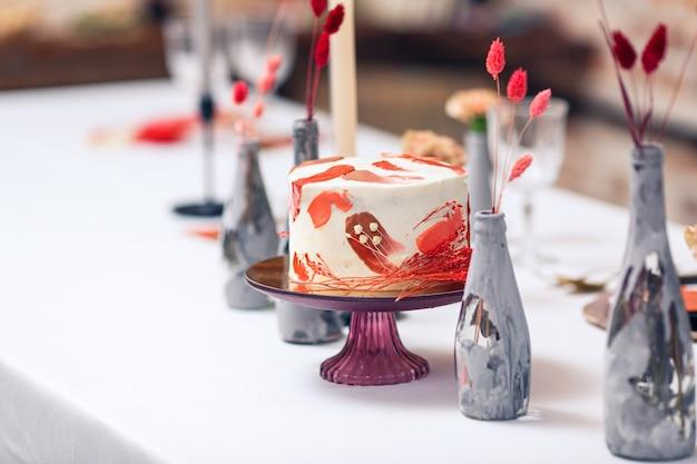 Feestelijke cake in het rood op feestzaal tafel. restaurant interieur.
