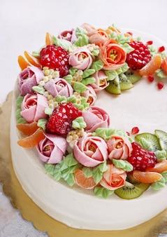 Feestelijke cake met crèmekleurige bloemen en fruit op een licht