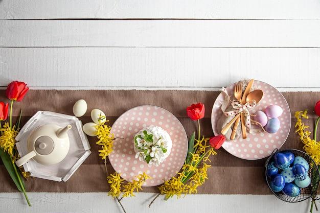 Feestelijke cake, theepot, eieren en bloemen op tafel. paasfeest en tafel instelling concept.