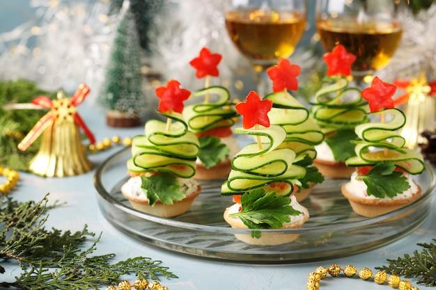 Feestelijke canapés in de vorm van kerstbomen gemaakt van komkommers en sterren van paprika op lichtblauw