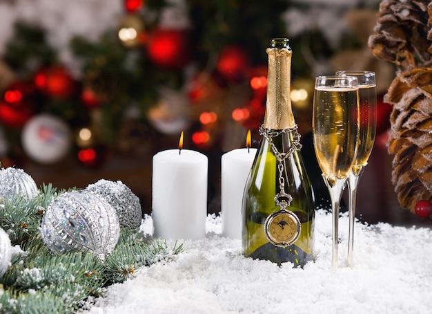 Feestelijke champagne en kaarsen op besneeuwde ondergrond
