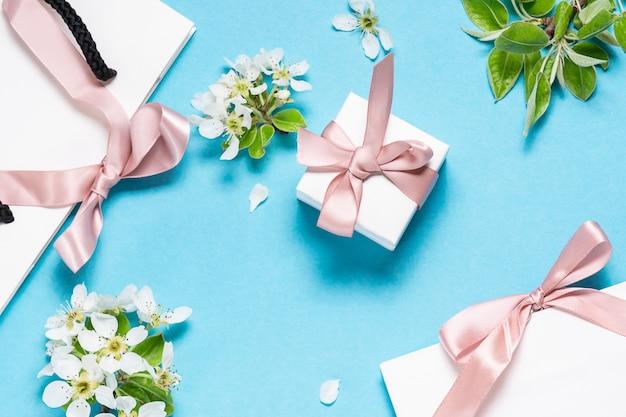 Feestelijke compositie met geschenkdoos, pakketten met strikken en prachtige lentebloemen op lichtblauwe achtergrond.