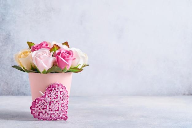 Feestelijke compositie met mooie delicate rozen bloemen in roze ronde doos met roze hartjes op lichtgrijze achtergrond. plat leggen, kopie ruimte.
