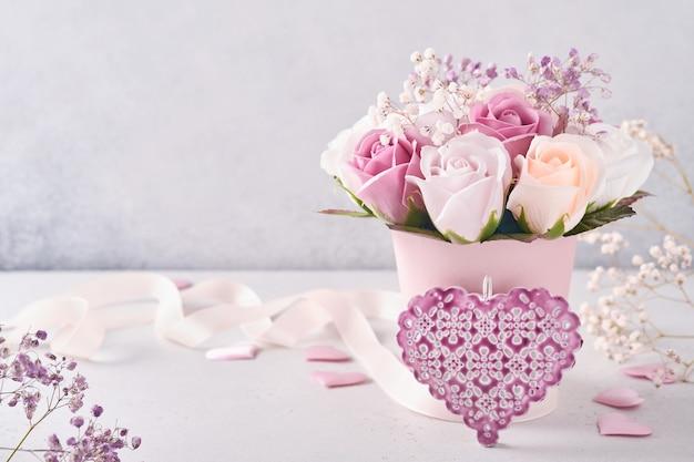Feestelijke compositie met mooie delicate rozen bloemen in roze ronde doos op lichtgrijze achtergrond. plat leggen, kopie ruimte.