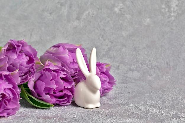 Feestelijke compositie met paarse tulpen en keramisch wit konijn