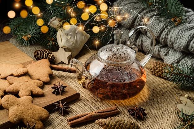 Feestelijke compositie met peperkoekkoekjes en glazen theepot in kerstdecor.