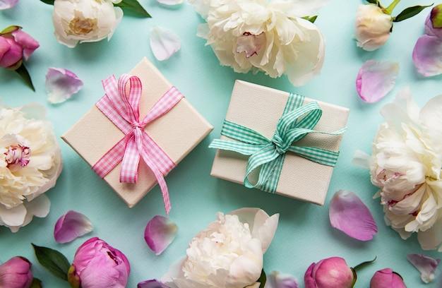 Feestelijke compositie op blauwe pastel achtergrond: pioenrozen bloemen, geschenkdozen. bovenaanzicht, kopieer ruimte.