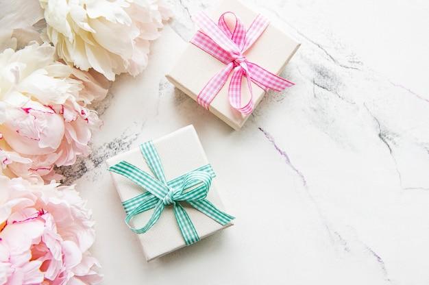 Feestelijke compositie op witte achtergrond pioenrozen bloemen geschenkdozen bovenaanzicht kopie ruimte