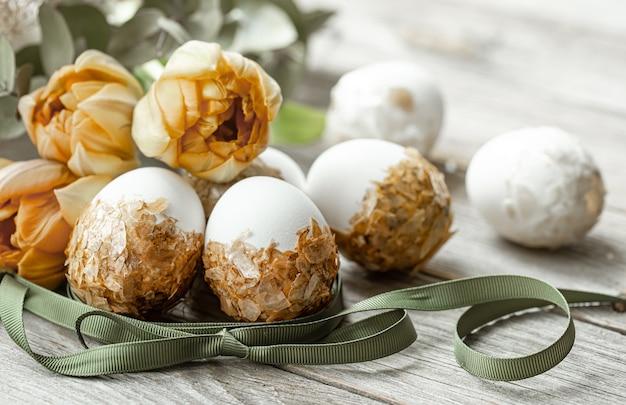 Feestelijke compositie voor de paasvakantie met versierde eieren en verse bloemen.