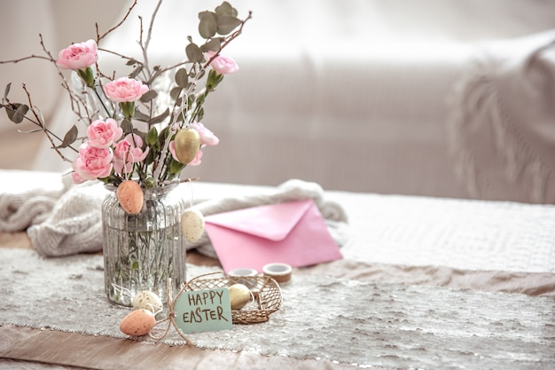 Feestelijke compositie vrolijk pasen met bloemen in een glazen vaas en decor details op de tafel kopie ruimte
