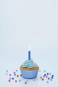 Feestelijke cupcake met blauwe glazuur en kaars op blauwe achtergrond, lege ruimte voor tekst bovenop. 3d-rendering. verjaardag wenskaart.