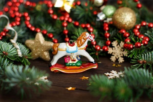 Feestelijke decoraties met hobbelpaard, kerstballen en sneeuwvlokken op hout