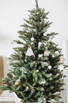 Feestelijke dennenboom versierd met speelgoed, geschenken, ballen