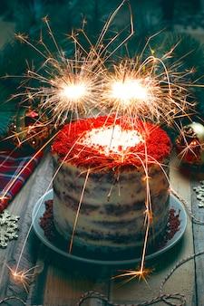 Feestelijke dessertverjaardag of valentijnskaart rode fluweelcake met vuurwerk
